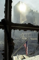 A solitary American flag hangs against the backdrop of debris that was once the World Trade Center in New York Tuesday, Sept. 11, 2001. Planes crashed into the upper floors of both World Trade Center towers minutes apart Tuesday morning, collapsing both 110-story buildings. (AP Photo/Graham Morrison)